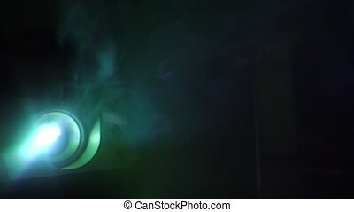 Motion picture projector in action in dark smoky room