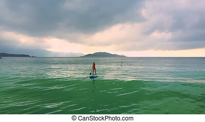 motion to girl standing on paddleboard among ocean