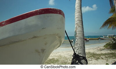 motion tracked timelapse along a rail, of fishing boats on the beach in isla mujeres mexico. beautiful colours.