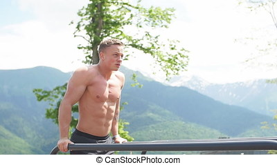 Motivated athletic man does bodyweight push ups at mountains...