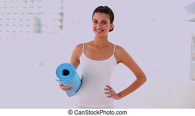 Motivated beautiful woman carrying mat