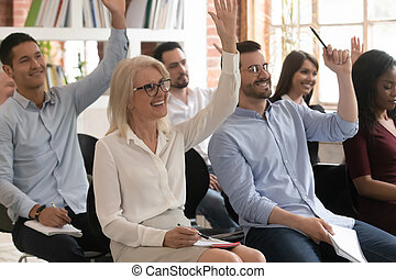 Motivated diverse employees raise hand participating in training
