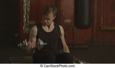 Motivated fit man training with dumbbells in gym - Muscular...
