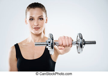 Motivated girl exercising with dumbbells on a grey background