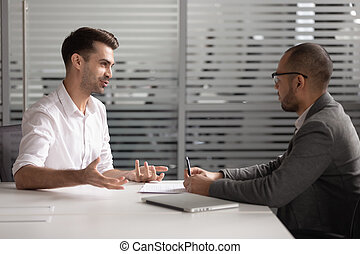 Motivated male applicant talk with recruiter at interview