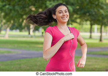 Motivated pretty woman jogging in a park