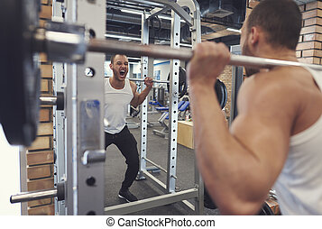 Motivated young athlete working out with barbell