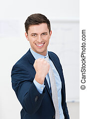 Motivated young businessman punching the air with his fists...