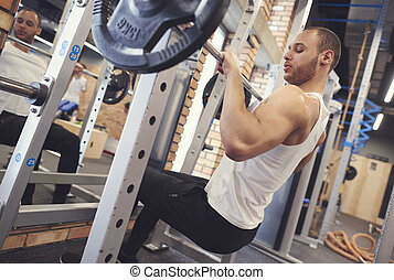 Motivated young man lifting barbell