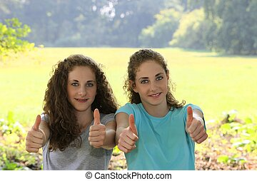Motivated young sisters giving a thumbs up