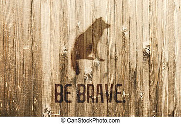 Sitting Wolf Burned in Wooden Planks. Text Be brave.