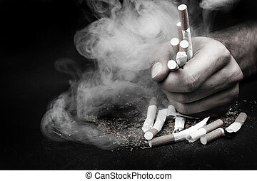 Destroyed cigarettes in hand with smoke on a black background