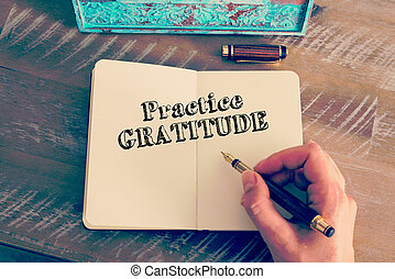 Motivational message PRACTICE GRATITUDE written on notebook