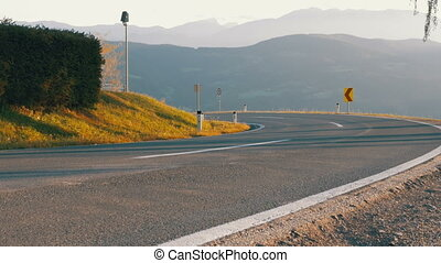 Moto Biker Rides on a Mountain Road from the Turn. Landscape view of the Alps Mountains, Austria