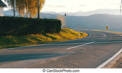 Moto Biker Rides on a Mountain Road from the Turn. Landscape...