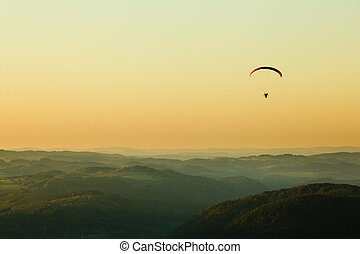 Moto paraglider above the landscape in sunset