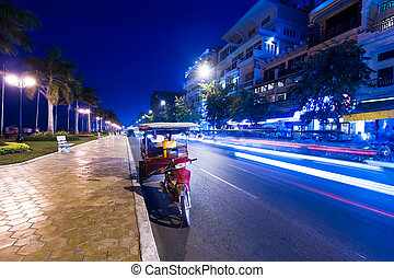 Moto taxi at evening asian city. Scene of night life at most popular tourist street near Mekong river in capital city Phnom Penh, Cambodia