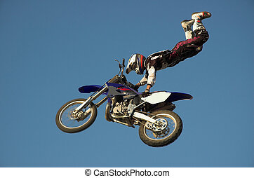 Moto X Freestyle rider high in sky with legs pointing up