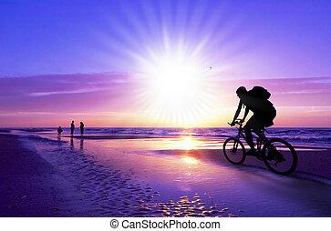 motociclista de montaña, en, playa, y, ocaso