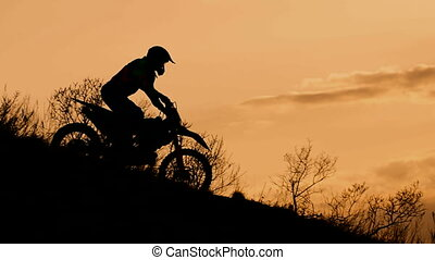 Motocross bike slides down a hill at sunset. Silhouette of...