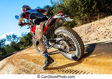 Motocross bike taking off on dirt road. - Rear view of...