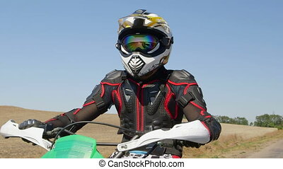 Motocross biker riding enduro motorcycle on country road...
