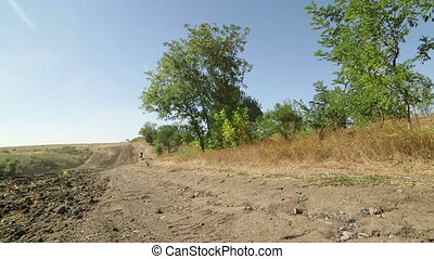 Motocross biker riding enduro motorcycle on dirt track...