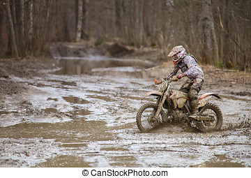 Motocross Challenge - Motocross driver on wet and muddy...