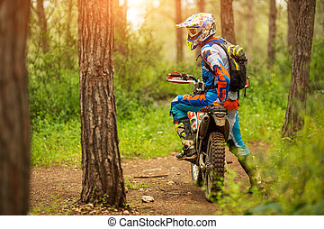 Motocross driver in the forest. motorcycle driver looks, concept, active lifestyle