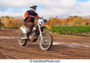 Motocross, enduro rider on dirt track. Extreme off-road race. Hard enduro motorbike. The forest behind him.