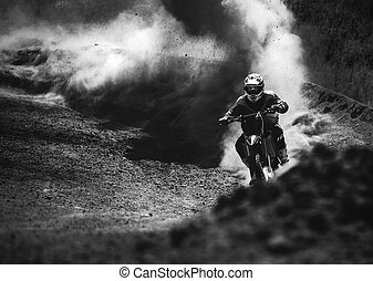 Motocross racer accelerating in dust track, Black and white photo