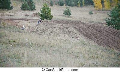 Motocross racer biker in blue jumpsuit jumping on track...