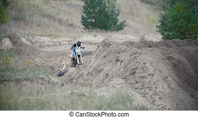 Motocross racer biker in blue jumpsuit jumping on track in...
