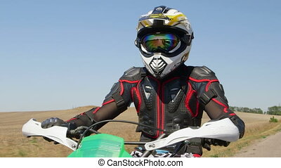Motocross racer in motorcycle gear riding bike on rural road