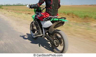Motocross racer in motorcycle protective gear riding enduro bike