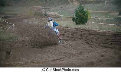 Motocross racer jumping. Rear view of biker on track in slow...