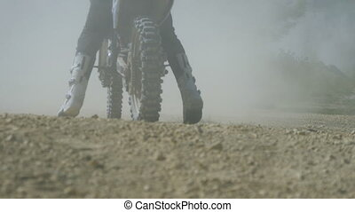 Motocross racer start riding at his dirt bike kicking up dirt and dust. Back view Slow motion