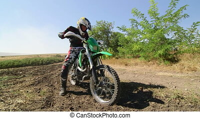 Motocross racer starting engine of his dirt bike riding away kicking up dust