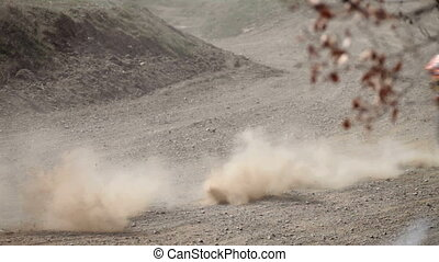 bikers race in dry, dusty conditions