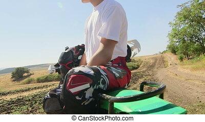 Motocross rider boy with his dirt bike looks afar