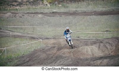 Motocross rider in a red jumpsuit chasing racer mxgirl on...