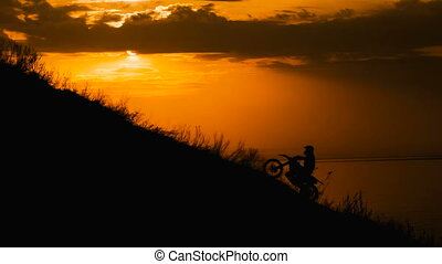 motocross rider storms obstacle. Climb up the hill on the road. Sunset painted the sky