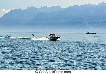 Motor boat and man wakeboarding on Lake Geneva in Lausanne