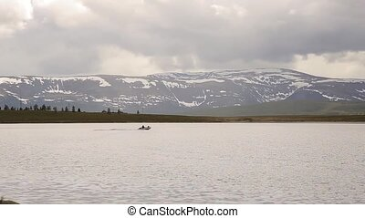 motor boat floats on a mountain lake, hiking and fishing in...