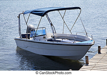 motor boat on jetty - White motor boat tied up at a seaside...