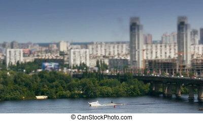 Motor boat on river and car traffic on bridge in Kiev timelapse