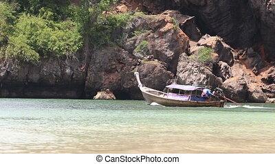 motor boat sailing past cliff