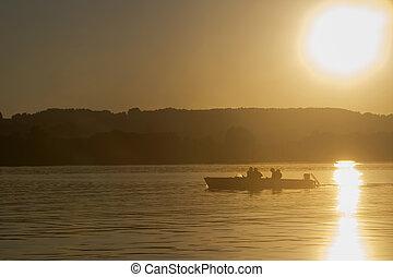 Motor boat, sunset at the lake