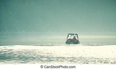 Motor boat with waving Russian flag cruising along hazy...