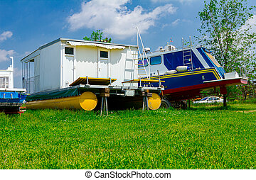 Motor boats are dry docked on the grass